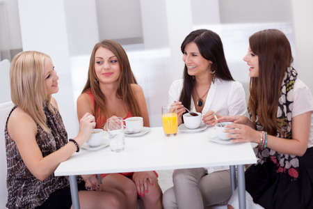Four stylish attractive young female friends seated at a table chatting over coffee photo