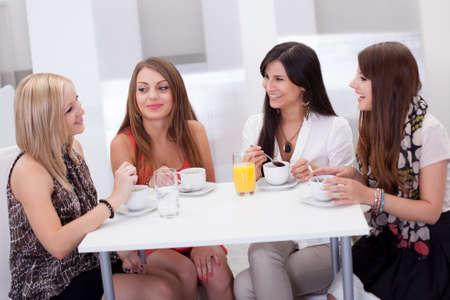 Négy stílusos vonzó fiatal nő barátai egy asztalnál beszélgetni egy kávé Stock fotó