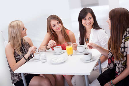 mujeres sentadas: Cuatro elegantes atractivas amigas jóvenes sentados en una mesa charlando con un café