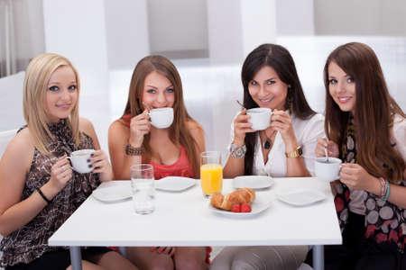 socializando: Cuatro elegantes atractivas amigas jóvenes sentados en una mesa charlando con un café