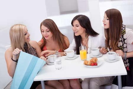 Vier jonge vrouwen vrienden zitten aan een salontafel te kijken naar winkelen aankopen in een draagtas in het bezit van een van hen Stockfoto