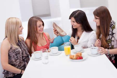 amigas conversando: Las mujeres discutiendo calzado juntos sentados en una mesa de café de la mañana mientras comparan sus compras comerciales