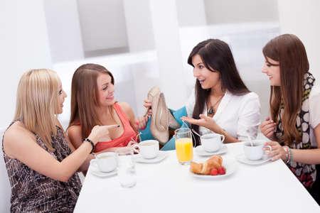 mujeres sentadas: Las mujeres discutiendo calzado juntos sentados en una mesa de caf� de la ma�ana mientras comparan sus compras comerciales