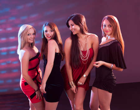 people partying: Group of glamorous young women in evening attire dancing together at a nightclub or disco Stock Photo