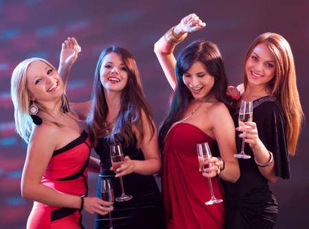 donna che balla: Gruppo di quattro donne alla moda in piedi in una fila tosta con flute di champagne Archivio Fotografico