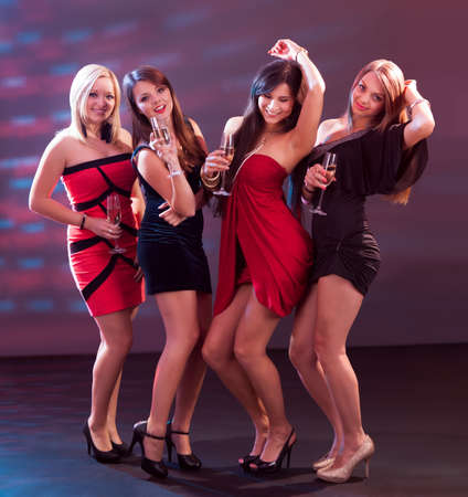 Groupe de quatre femmes élégantes debout dans une rangée de grillage avec flûtes de champagne Banque d'images - 15720013