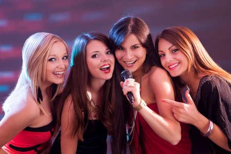 gente cantando: Cuatro muchachas hermosas elegantes cantando karaoke en el club