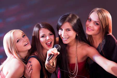 people singing: Four beautiful stylish girls singing karaoke at the club Stock Photo