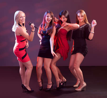 Group of glamorous young women in evening attire dancing together at a nightclub or disco photo