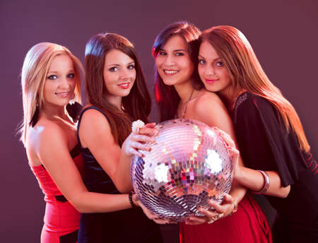 sexy girls party: Four attractive females are holding disco ball
