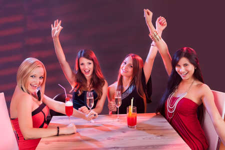 jubilation: Glamorous young women celebrating in a nightclub sitting around a table laughing and raising their arms in the air in jubilation