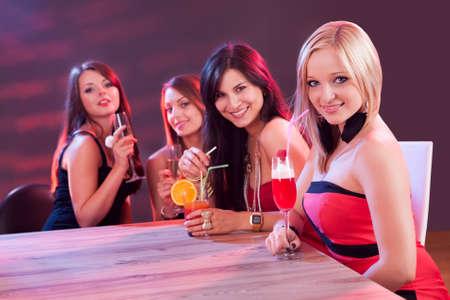 Amies jouissant d'une soirée cocktails assis à une table ayant en boîte de nuit Banque d'images - 15702753