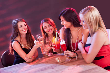 night out: Female friends enjoying a night out sitting having cocktails at a table in a nightclub