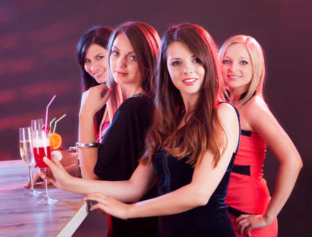night club: Four beautiful fashionable women on a night out standing at a bar counter with their drinks