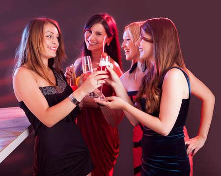 socializando: Grupo de cuatro hermosas felices jóvenes amigas celebrando en una discoteca con copas de cóctel en la mano Foto de archivo