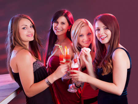 attractive lady: Group of four happy beautiful young female friends celebrating in a nightclub with glasses of cocktail in their hands Stock Photo