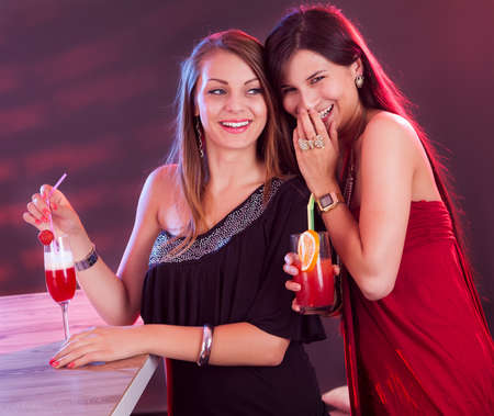 people partying: Two beautiful long haired female friends partying at a bar counter with cocktails in their hands under colorful lighting in a nightclub Stock Photo