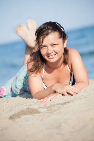 Portrait of beautiful young woman relaxing at the beach photo