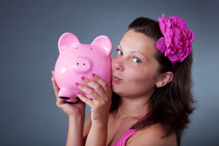 nestegg: Cute pretty woman with a large flower in her hair nuzzling up to a large pink piggybank