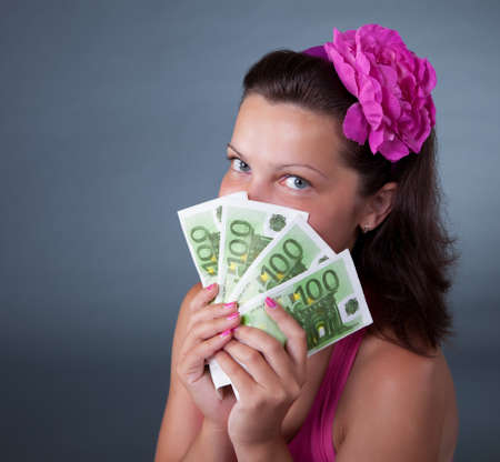 finance girl: Wealthy woman with beautiful eyes holding a fan of 100 euro notes in front of her face against a dark grey studio background with copyspace