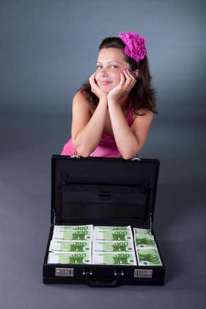 billets euro: Jolie femme souriante assise sur le sol avec une mallette rempli de billets en euros 100 sur un fond de studio gris