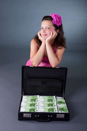 Pretty smiling woman sitting on the floor with a briefcase packed full of 100 euro notes on a grey studio background photo