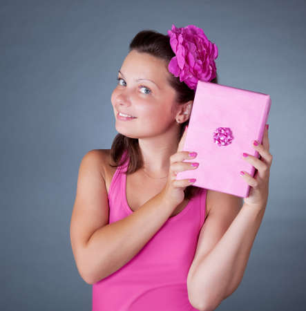 tantalizing: Cheeky beautiful woman with a flower in her hair holding up a decorative pink gift on a grey studio background