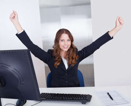 arms above head: Jubilant businesswoman raises her arms above her head in celebration of her success sitting in her office