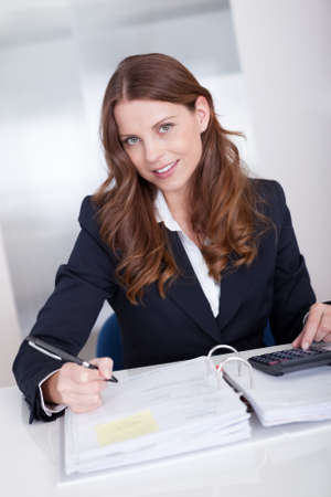 bookkeeping: Smiling stylish businesswoman sitting at her desk using a calculator and completing an analysis sheet or journal