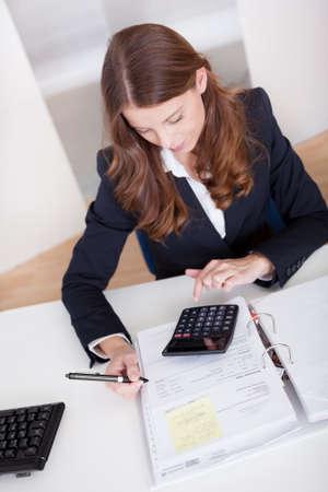Glimlachend stijlvolle zakenvrouw zittend aan haar bureau met behulp van een rekenmachine en het invullen van een analyse blad of tijdschrift