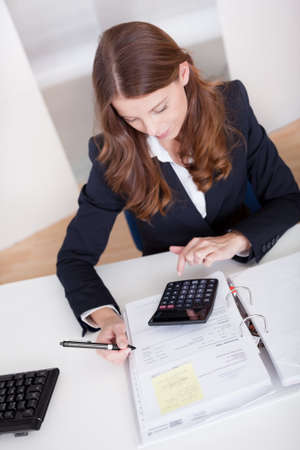 auditor�a: Sonriente mujer de negocios elegante sentado en su escritorio con una calculadora y completar una ficha de an�lisis o revista