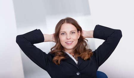 secretaria sexy: Jubilant empresaria levanta los brazos por encima de su cabeza en la celebraci�n de su �xito sentada en su oficina Foto de archivo