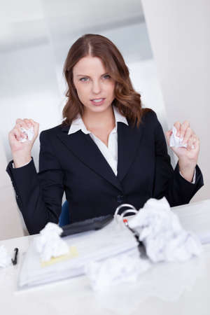 High angle view of a businesswoman seated at her desk crumpling paper in frustration as she is incapable of arriving at a solution Stock Photo - 16336639