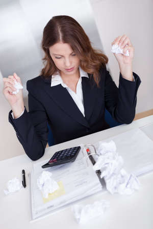 High angle view of a businesswoman seated at her desk crumpling paper in frustration as she is incapable of arriving at a solution Stock Photo - 16336661