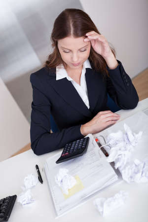 High angle view of a businesswoman seated at her desk crumpling paper in frustration as she is incapable of arriving at a solution Stock Photo - 16336648