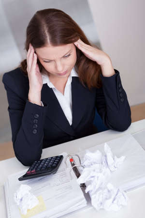 High angle view of a businesswoman seated at her desk crumpling paper in frustration as she is incapable of arriving at a solution Stock Photo - 16336617