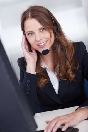 Smiling receptionist or call center worker sitting typing photo