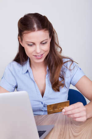 Young woman seated at her laptop entering her credit card details while shopping online photo
