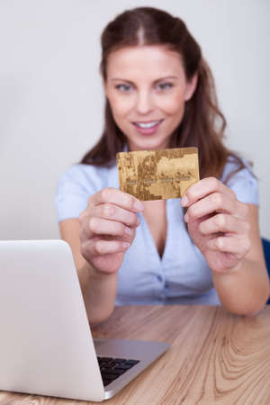 Young woman seated at her laptop entering her credit card details while shopping online Stock Photo - 16336677