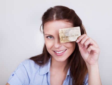 Young woman seated at her laptop entering her credit card details while shopping online Stock Photo - 16336674