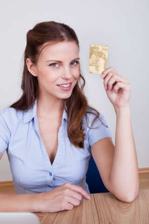 Young woman seated at her laptop entering her credit card details while shopping online Stock Photo - 16336637