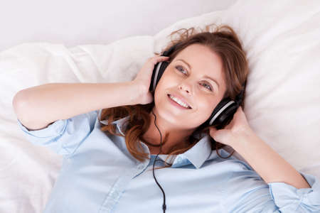 Woman relaxing on her bed in a casual blue shirt wearing stereo headphones bed listening to music Stock Photo - 16336659