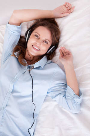 Woman relaxing on her bed in a casual blue shirt wearing stereo headphones bed listening to music Stock Photo - 16336666