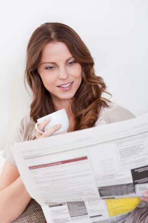 newspaper reading: Woman reading the newspaper while drinking a refreshing cup of morning coffee