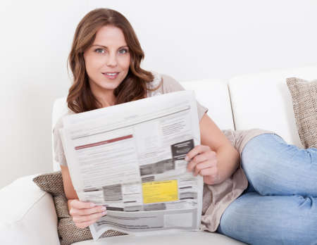 Woman reading the newspaper while drinking a refreshing cup of morning coffee photo