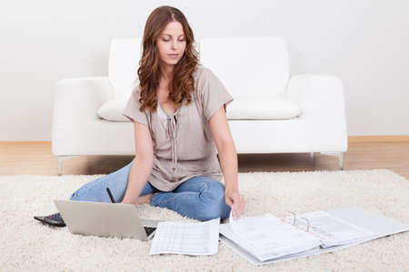 Smiling young woman sitting on the carpet with her papers and a laptop working in the living room Stock Photo - 16350865