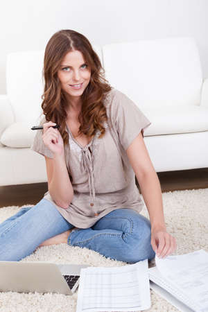 Smiling young woman sitting on the carpet with her papers and a laptop working in the living room Stock Photo - 16336646