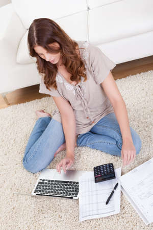 Smiling young woman sitting on the carpet with her papers and a laptop working in the living room Stock Photo - 16336686