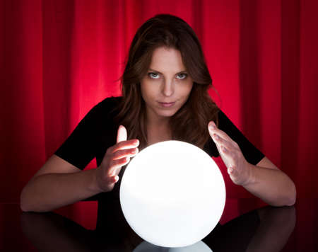 Beautiful young fortuneteller holding her hands around a glowing ball as she foretells the future and what it holds photo