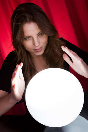 Beautiful young fortuneteller holding her hands around a glowing ball as she foretells the future and what it holds Stock Photo - 16336668